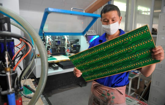 A staff member works in a circuit board manufacturing facility in Hangzhou in eastern China's Zhejiang province.