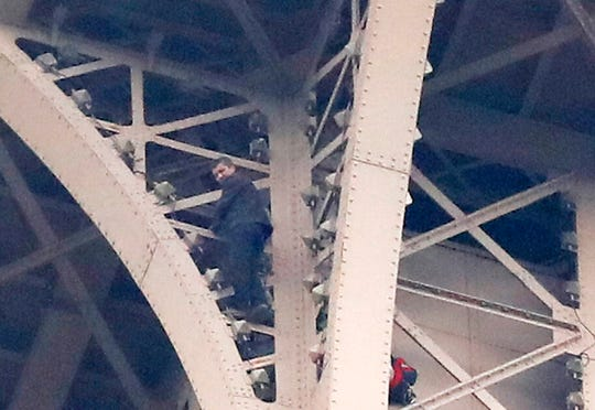 A climber is pictured between two iron columns of the Eiffel Tower while a rescue worker is partially seen at right, Monday, May 20, 2019 in Paris. The Eiffel Tower has been closed to visitors after the man has tried to scale it.