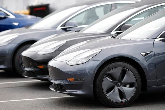 In this Sunday, May 19, 2019, file photograph, a line of unsold 2019 Model 3 sedans sits at a Tesla dealership in Littleton, Colo.
