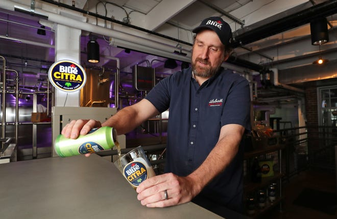 Ryan Brady, who grew up in Troy, attended UM, and is now Labatt USA's first-ever brewmaster, pours a Labatt Blue Citra at The Labatt Brew House in Buffalo, N.Y. Brady developed the new mass-market beer in the company's innovation brewery.