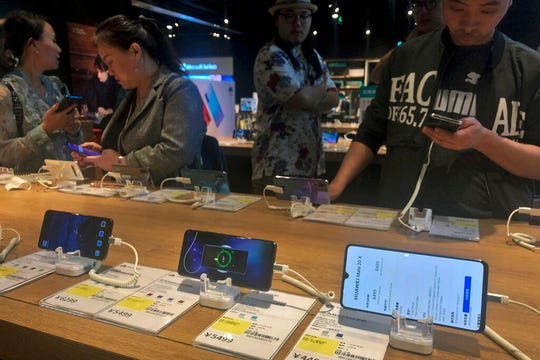 People try out Huawei smartphone models on display at an electronic store in Beijing, Monday, May 20, 2019. Google assured users of Huawei smartphones on Monday the American company's basic services will work on them following U.S. government curbs on doing business with the Chinese tech giant.