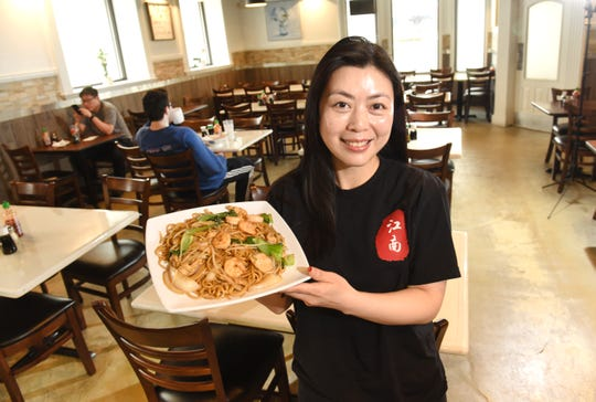 Vicky Chin, co-owner, Jiang Nan Noodle House , holds one the restaurant's favorites the Dragon La-Mian made with wok fried shrimp, vegetables and noodles.