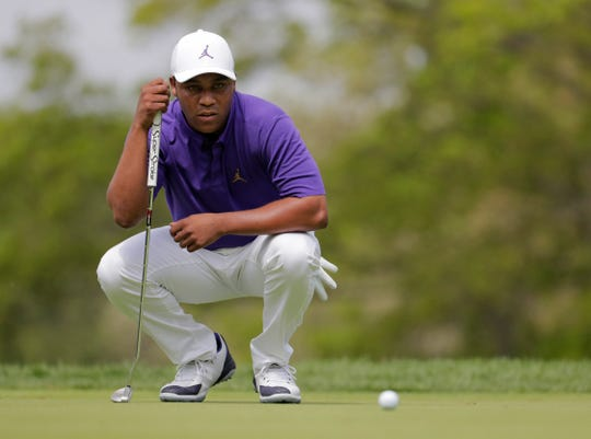 Harold Varner III lines up a putt on the third hole Sunday.