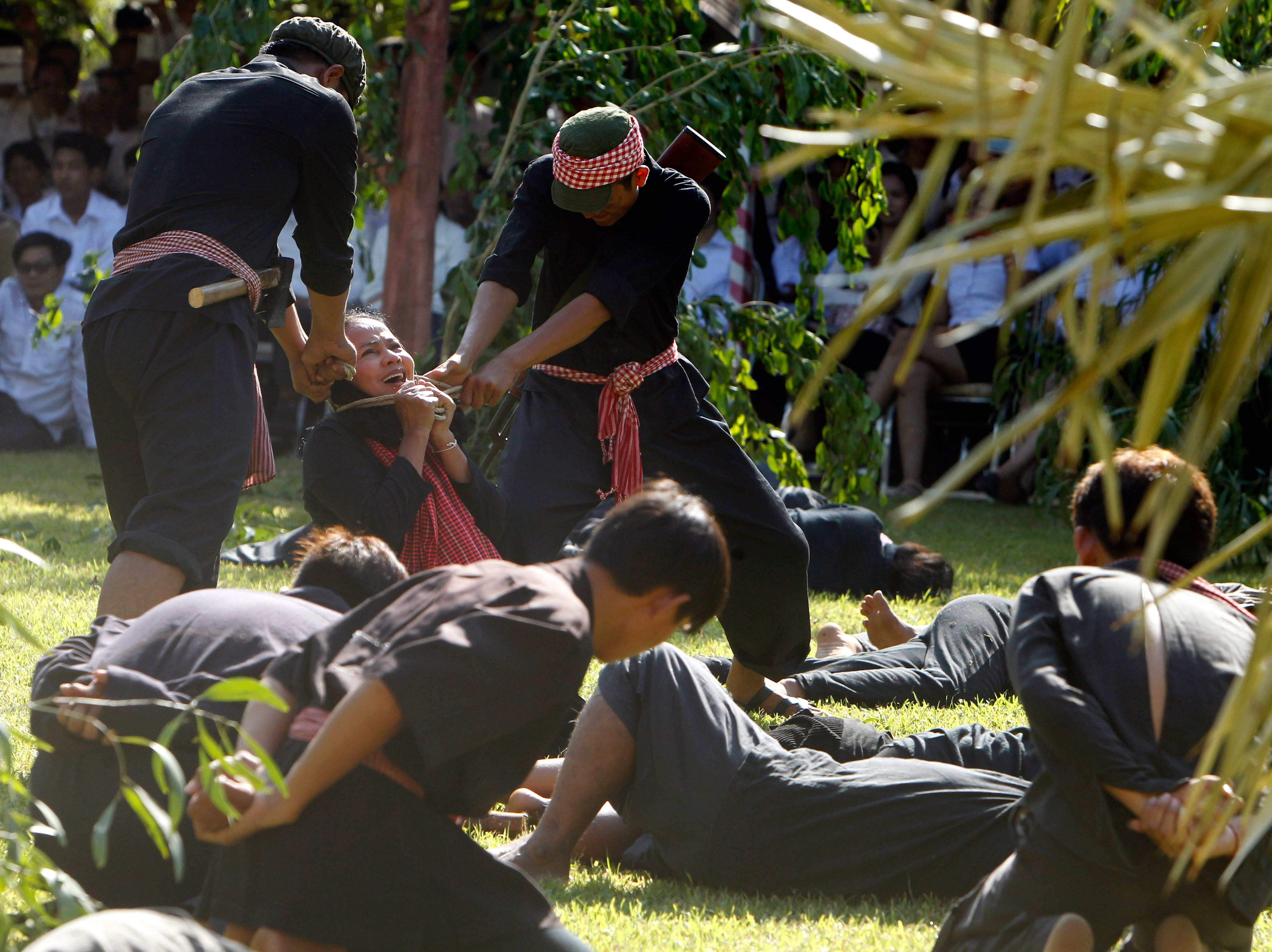 """Cambodian students from Royal University of Fine Arts re-enact torture and execution by the Khmer Rouge during their reign of terror in the 1970s in an event hosted by the ruling Cambodian People's Party to mark the annual Day of Anger at Choeung Ek, a former Khmer Rouge """"killing field,"""" outside Phnom Penh, Cambodia, Monday, May 20, 2019."""