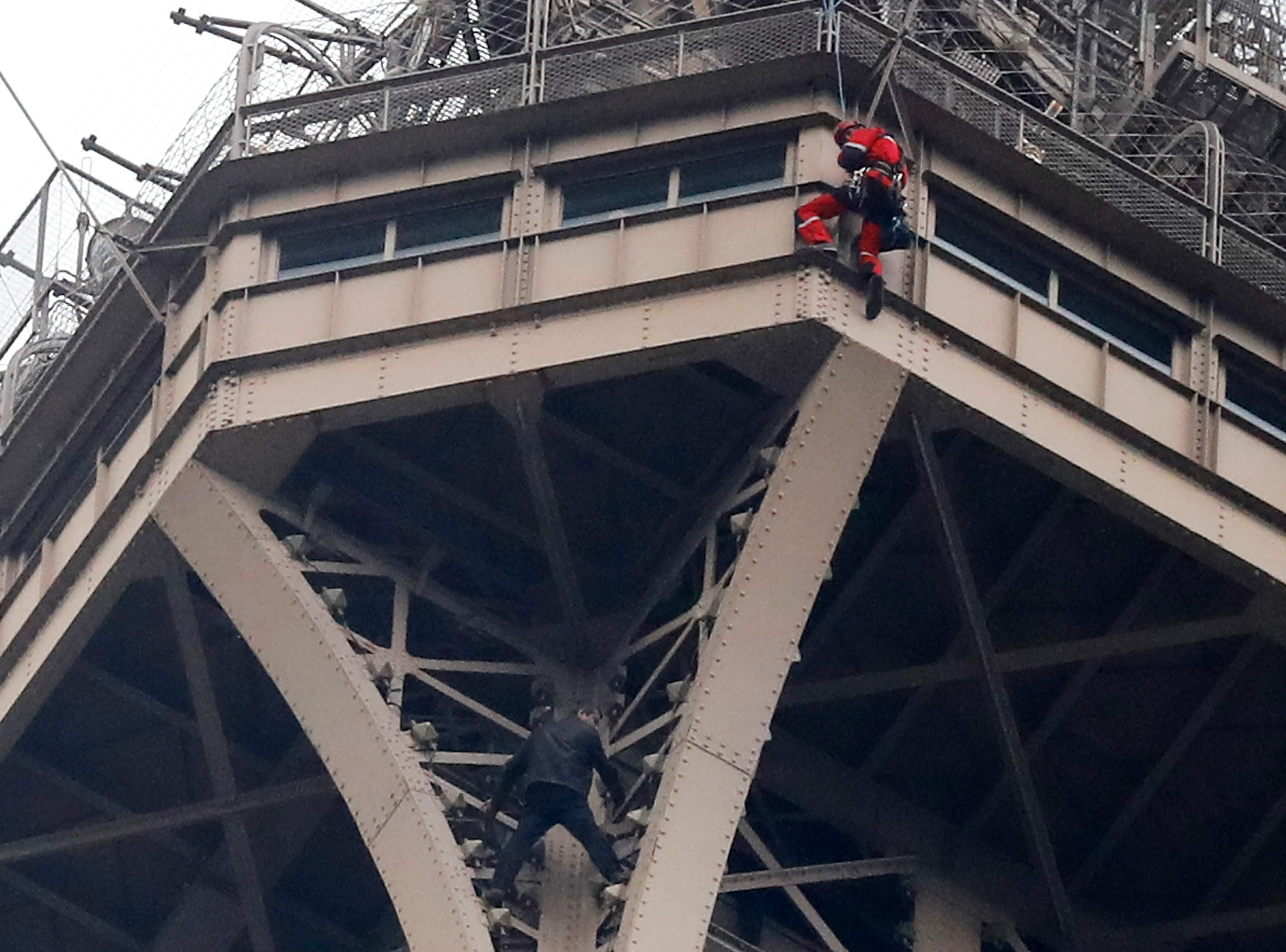 A rescue worker, top, in red, hangs from the Eiffel Tower above a climber standing between two iron columns Monday, May 20, 2019 in Paris. The monument was evacuated after the climber scaled nearly to the top of the tower before eventually surrendering.