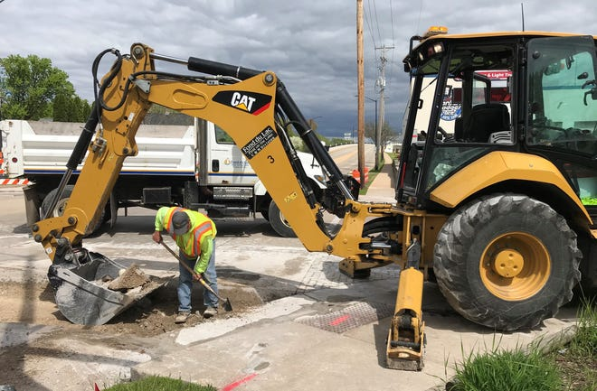 A Department of Public Works crew digs up a brick crosswalk Monday along Johnson Street at Chestnut Street. . The bricks are causing problems and will be replaced with colored concrete stamped to look like bricks. The project will snarl up traffic in the area with the closing of the Johnson Street Bridge.