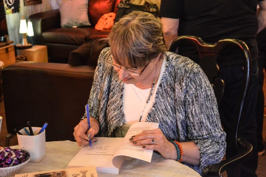 """Author Cindy Kolbe signs a copy of """"Struggling with Serendipity"""" during a book talk and signing at Mutach's Wine Room in Marblehead. The book has local connections to Green Springs, Clyde, Toledo, and Tiffin."""