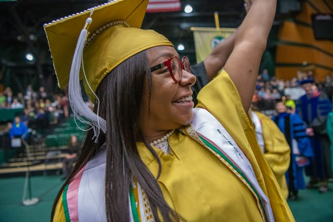 Graduate Janae Brown waves to friends and family as she enters Moby Arena at the start of the CSU College of Liberal Arts 1 commencement ceremony on Sunday, May 19, 2019, in Fort Collins, Colo.
