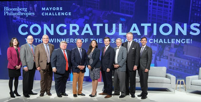 Fort Collins Mayor Wade Troxell, third from left, and South Bend, Indiana, Mayor Pete Buttelieg, fourth from right, who is running for president, at the Bloomberg Philanthropies Mayors Challenge ceremony.