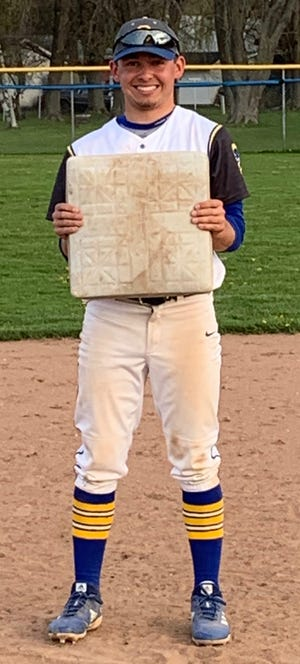 Bennett Frazer of Oconto holds up a base after breaking the school record for career stolen bases on May 13.