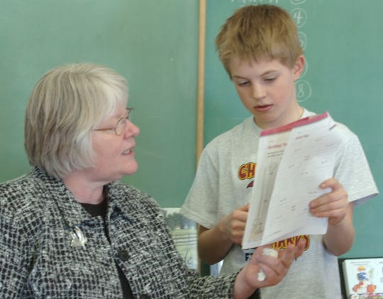 Susan Luinstra answers a homework question for fifth-grader Marshall Willekes in 2007. Luinstra is retiring after 38 years teaching at Bynum School.