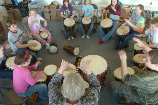 Lead by teacher Susan Luinstra, bottom, the Bynum student body in 2007 engage in a drumming session, one of their favorite group activities.