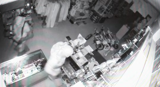 A photo of surveillance footage shows two people burglarizing the Champion Sporting Goods store in Mangilao.