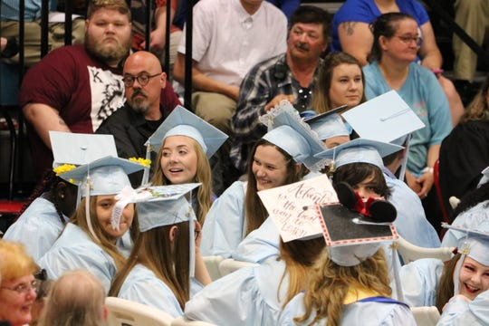 Brianna Utley and Hannah Turner turn around to watch the band play at graduation.