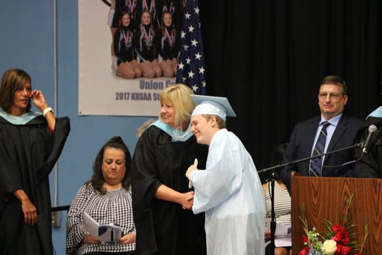 Nick Eunice smiles as he receives his high school diploma at graduation.