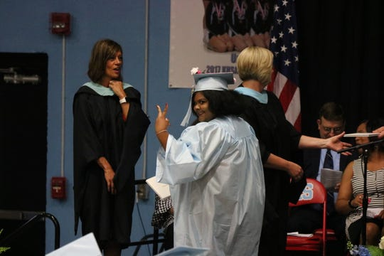 Hannah Carey throws up a peace sign as she receives her diploma at graduation.
