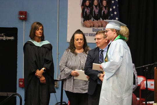 Ben Clements receives his diploma at graduation.