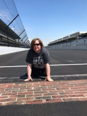 Andrea Preston kisses the bricks at Indianapolis Motor Speedway, a place she has loved since she first visited about 30 years ago. Now it also comforts her as she battles a condition that makes it hard for her to breathe.