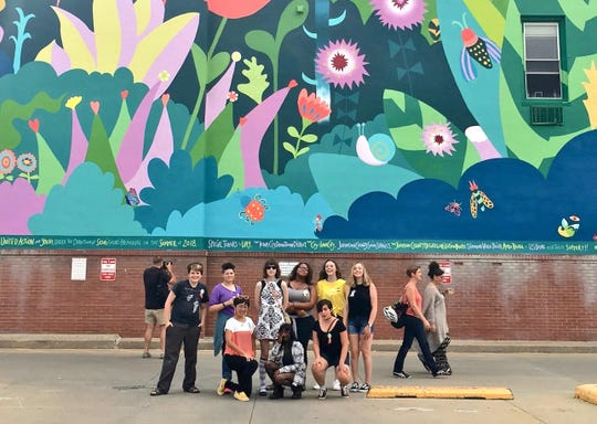 "community members pose in front of the ""Coexist"" mural in downtown Iowa City."
