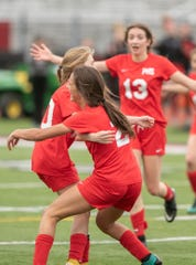 Pinckney's Gabrielle Hackett, left, and Zoe Moretti (13) congratulate Solana Kelly, center, on Kelly's game-winning goal with 3:50 left in a 2-1 victory over Dexter on Monday, May 20, 2019.