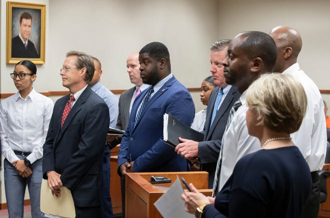 The six Louisville police officers and their attorneys stand before the judge during an arraignment on felony theft charges. May 20, 2019