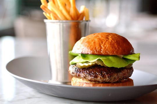 The Classic Burger, made with prime beef, Bibb lettuce, spicy pickles,  grilled onions and grocery sauce at Butchertown Grocery.