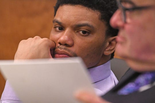 Deshawn Dowdell looks at evidence as his defense attorney Angelo Lonardo pages through photos Monday during Dowdell's murder trial.