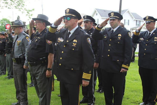 Former Marion Police Chief Bill Collins salutes a memorial, which was built to honor the memory of fallen law enforcement officers in Marion County.