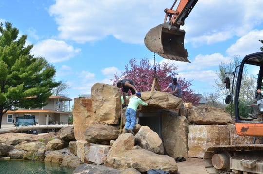 Construction workers move huge pieces of limestone into place to create a waterfall and grotto at the new lagoon at the American Resort in the Wisconsin Dells.