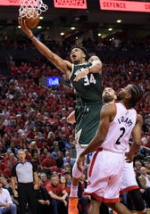 Bucks forward Giannis Antetokounmpo rises for a basket over  Kawhi Leonard.