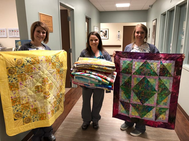 The Hill 'N Hollow Quilters donated 16 quilts this month to the Women's Center Nursery at Baxter Regional Medical Center. Pictured are: (from left)Haley Cotter; Haley Tyler with the stack of quilts; and Kelsie Lovan,with abatik baby quilt. Along with quilting for the community, the guild will host its biennial Autumn in the Ozarks quilt show Oct. 17-19 at Baxter County Fairgrounds. For more information, visit the group's website atwww.hillnhollowquilters.com.