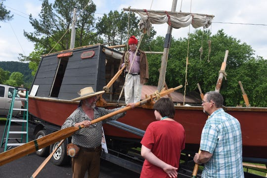 Early Arkansaw Reenactors Association member Jim Thompson (far left) holds one of the oars on the Aux Arc, a replica 19th century keelboat, Saturday in Norfork.