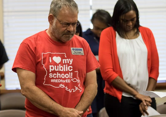 Roy Hodges bows his head during the invocation before the Monroe City School Board meeting on May 20 to vote on the establishment of a charter school in Monroe, La.