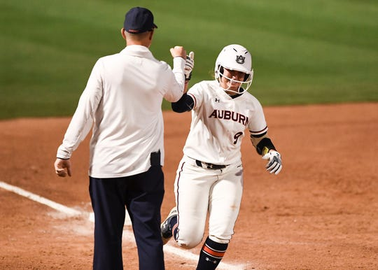 Auburn's Tannon Snow (9) high-fives coach Mickey Dean as she rounds third base against Colorado State on Friday, May 17, 2019, in Tucson, AZ.