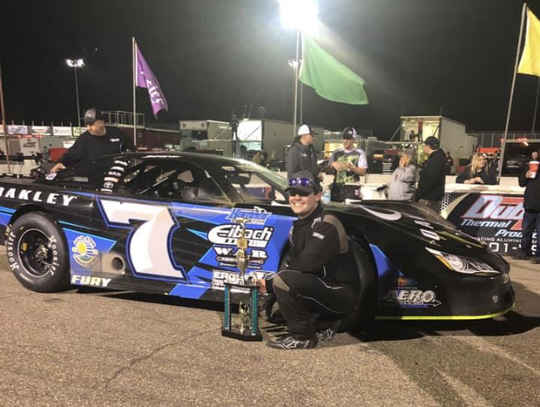 Jackson Boone poses with car and trophy after a podium finish earlier this year.