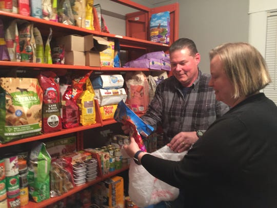 Brian Van Hook and Stephanie Hornback, volunteers for the Passaic County Society for the Prevention of Cruelty to Animals, put pet food in a plastic bag for a client of the nonprofit's pantry in Hawthorne on May 13.