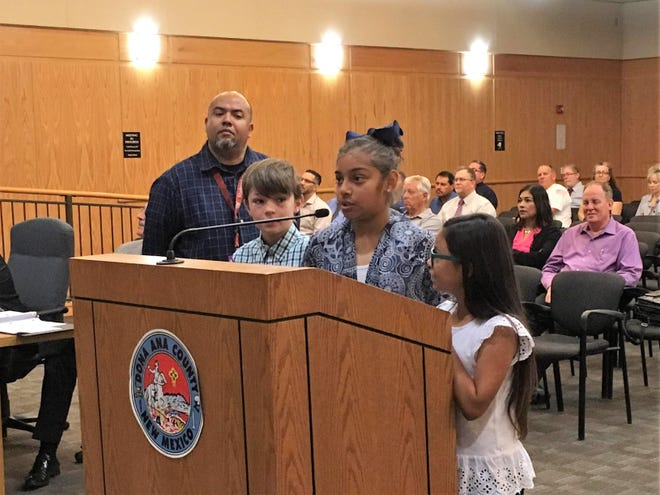From left, third grade teacher Henry Jasso with students Dylan Selby, Zoey Martinez, and Jaliene Rodriguez from Doña Ana address Doña Ana County commissioners on Tuesday, May 14, 2019.