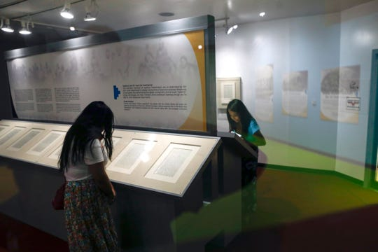 Members of the media inspect the pages of the Navajo-U.S. Treaty of 1868 on June 1, 2018 at the Navajo Nation Museum in Window Rock, Arizona.