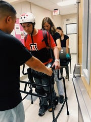 Jordan Lo undergoes eksoskeleton gait training in physical therapy.