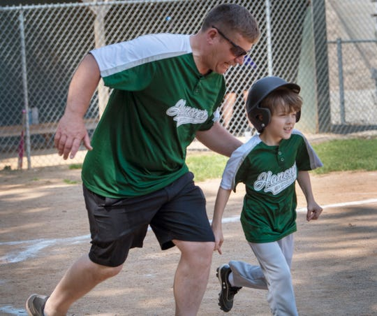 Coach Mike Cooper, left, gives Hanover player Jamie Davis some tips as he runs on to the field during a Challenger  Division Little League game between Hanover and Dillsburg at the Eagle Field in Hanover.