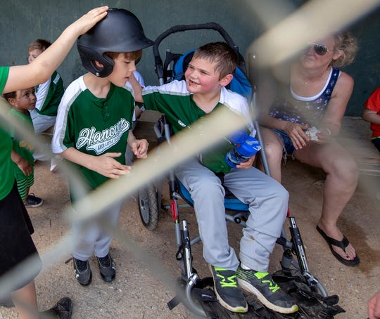 Jamie Davis, left, get his batting helmet on with Max Brown, while Max's mother Kristin, right, looks on during a Challenger Division Little League game between Hanover and Dillsburg at the Eagle Field in Hanover.