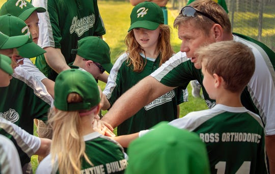 Hanover coach Mike Cooper opens the game with a huddle during a Challenger Division Little League game between Hanover and Dillsburg at the Eagle Field in Hanover.