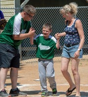 From the left, coach Mike Cooper helps Max Brown through home plate with his mother Kristin during a Challenger Division Little League game between Hanover and Dillsburg at the Eagle Field in Hanover.