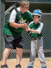 Hanover coach Mike Cooper helps Braden Warring with his batting skills during a Challenger Division Little League game between Hanover and Dillsburg at the Eagle Field in Hanover.