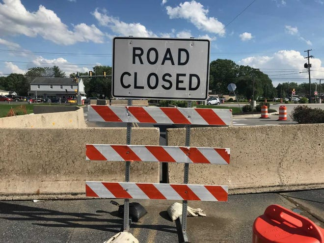 A road closed sign and barricades prevent traffic from using Route 422 in Palmyra, where a sinkhole formed after Sunday's heavy rains.
