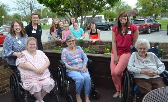 Members of Girl Scout Troop 11592 visited Genoa Retirement Village on May 16 to help residents and staff plant flowers outside the building. Pictured are, in front, seated: Carole Sayre, Sandra Schneider, and Ina Steward. In front, standing: Kelsey Rupley, Guest Relations; Leslie Ryan, Community Service Representative; and Bryanna Lee, Executive Director. In back: Addison Lenz, Emma Kable, Paigelynn McWatters, Elizabeth Buffington, Taylor Costley, and Leah Beard.