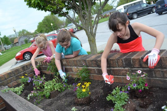 Girl Scout Troop 11592 members Paigelyn McWatters, Taylor Costley, and Leah Beard plant flowers at Genoa Retirement Village. The activity was one of many community outreach events hosted by Genoa Retirement Village each year.