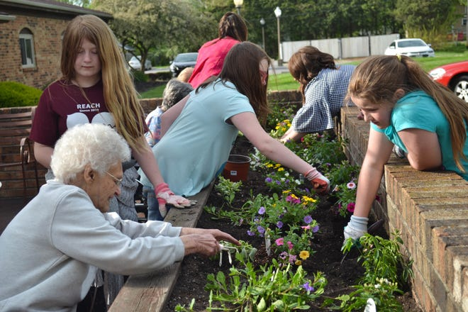 Ina Stewart, lower left, plants flowers with members of Girl Scout Troop 11592 at Genoa Retirement Village in May 2019, a year prior to a COVID-19 outbreak at the same facility.