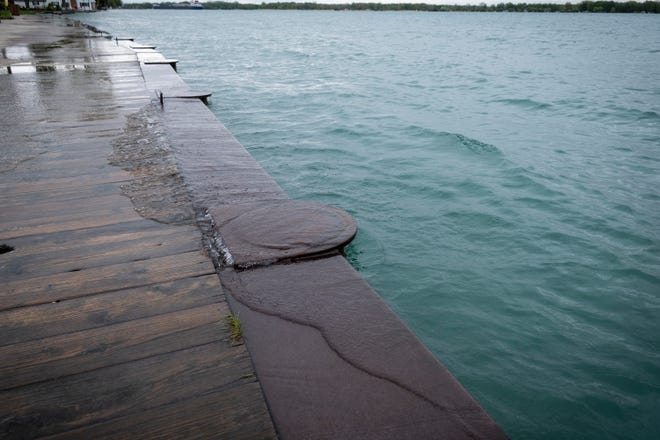Waves lap from the St. Clair River over the boardwalk in Algoanc Monday, May 20, 2019.