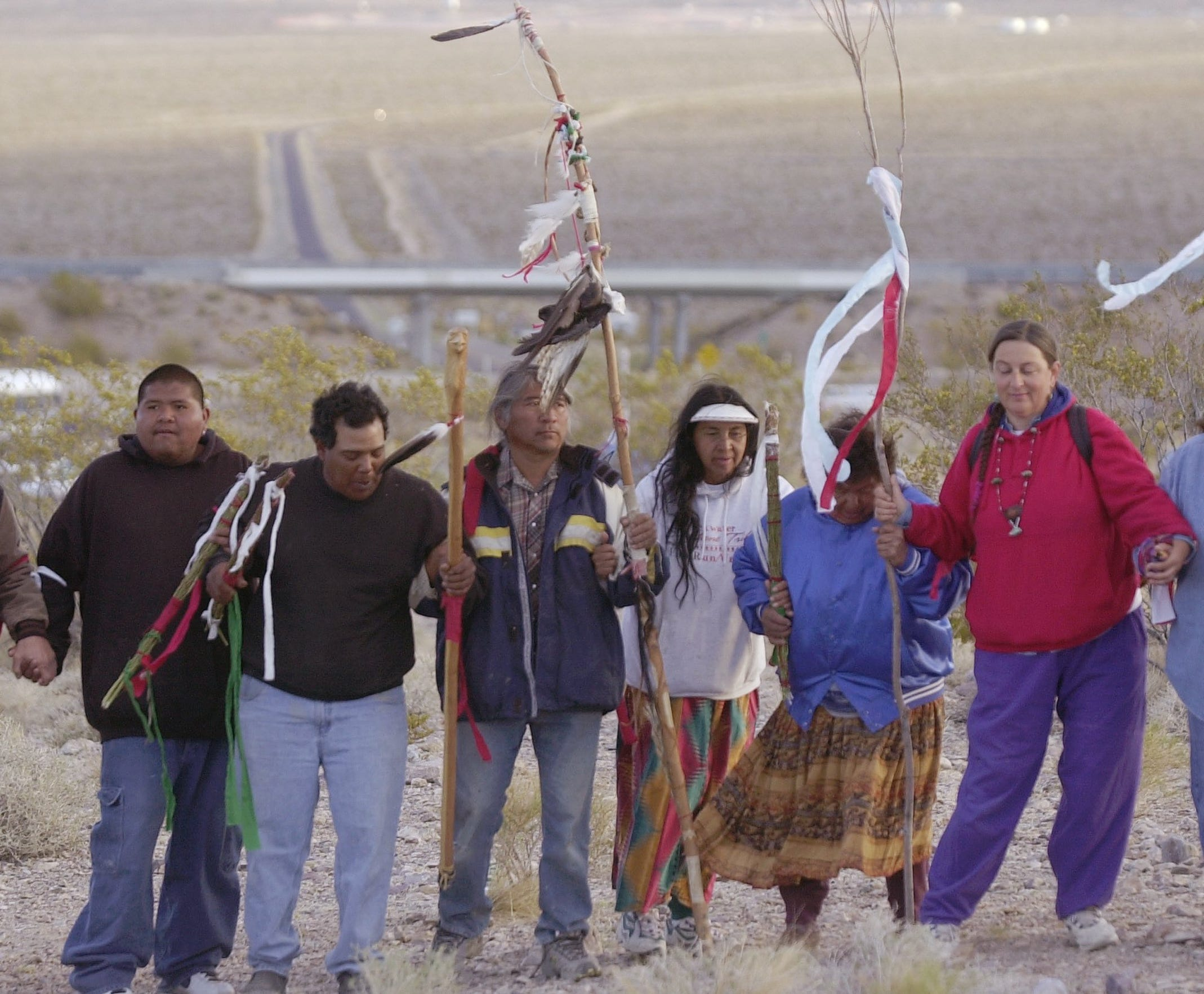 Johnnie Bobb, third from left, takes part in a ceremony near the gates to the Nevada Test Site, in background, and the proposed Yucca Mountain  nuclear waste dump on May 11, 2002. Seventeen years later, Bobb and other Native Americans continue to protest the storage of nuclear waste at the site.